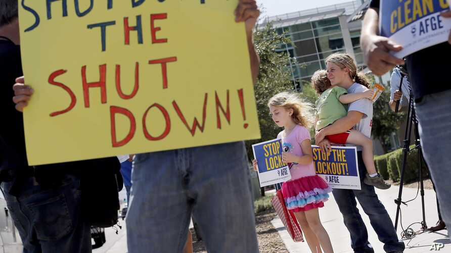As the federal government shutdown continues, Tory Anderson, right, with her kids Audrey, 7, and Kai, 3, of Goodyear, Ariz., join others as they rally for the Alliance of Retired Americans to end the shutdown, Oct. 9, 2013.