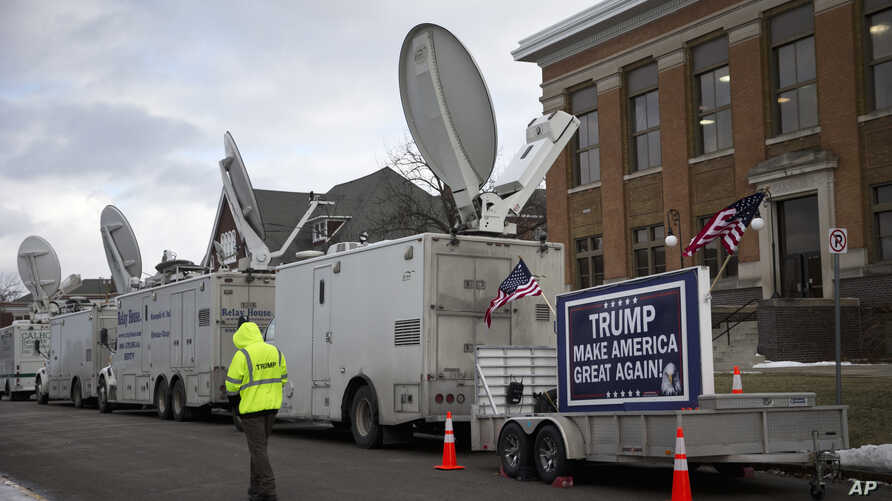 FILE - A trailer with a sign supporting Republican presidential candidate Donald Trump, and satellite trucks, are parked on the campus of Drake University in Des Moines, Iowa, Jan. 28, 2016, where Trump is scheduled to hold a campaign event.