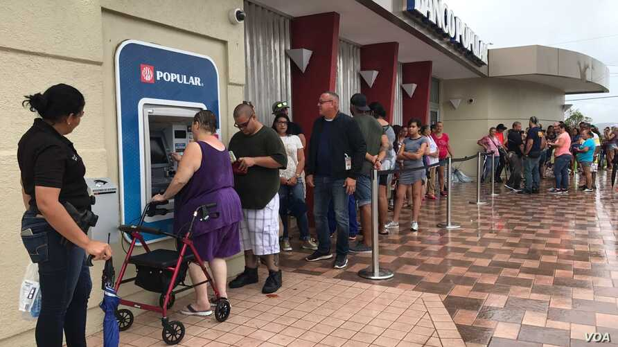 Residents of Ponce, Puerto Rico, line up at an ATM in hopes of getting some cash. More than a week after Hurricane Maria struck, residents are waiting in long lines to withdraw money and for gasoline.