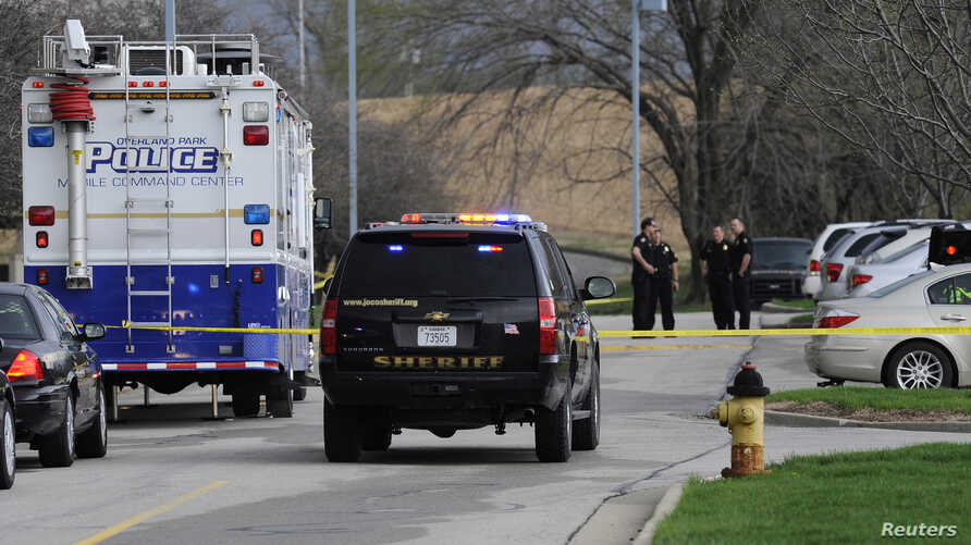 Police officers gather at the scene of a shooting at the Jewish Community Center of Greater Kansas City in Overland Park, Kansas, April 13, 2014.