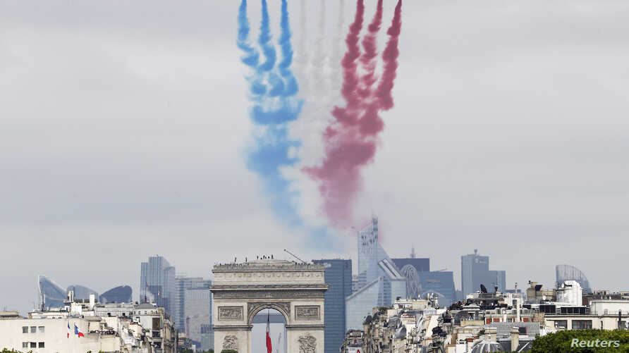 Nine alphajets from the French Air Force Patrouille de France release France's national colours trail as they fly above the Arc de Triomphe and the Champs-Elysees avenue during the traditional Bastille Day military parade in Paris July 14, 2014.   RE