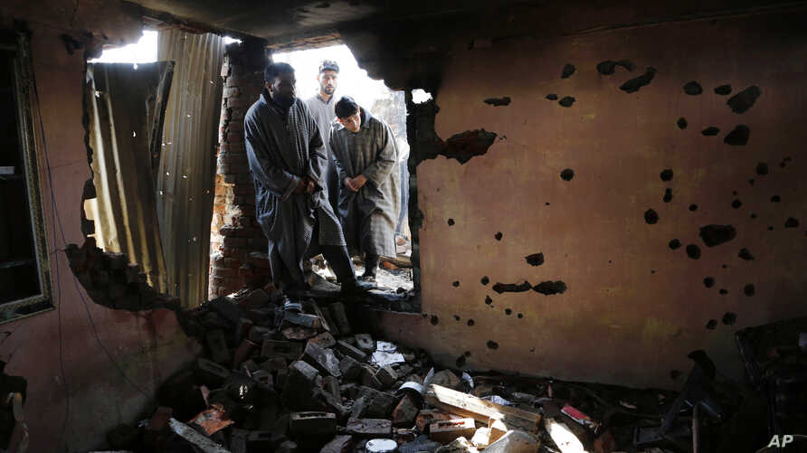 FILE - Kashmiri villagers inspect a house damaged during a gun battle between Indian soldiers and suspected militants in Dadsar on the outskirts of Srinagar, Indian-controlled Kashmir.