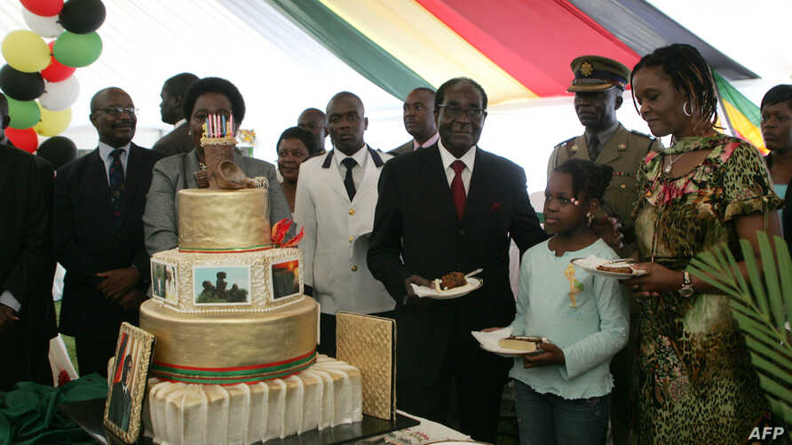 Zimbabwe President Robert Mugabe (4th R) and first lady Grace Mugabe (2nd R) stand with the presidents birthday cake among guests on the occasion of his 89th birthday celebrations held in his honour at the State House, the eve of his birthday, Februa