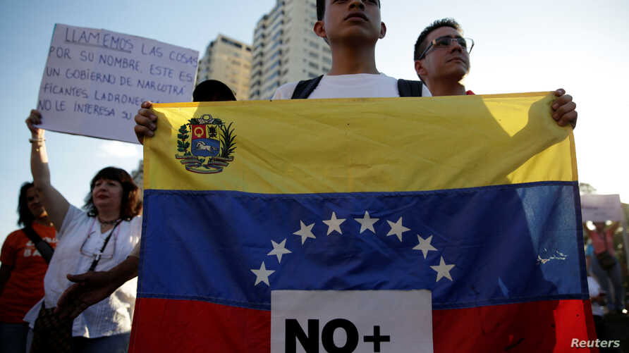 "An opposition supporter holds a Venezuelan flag with a sign that reads ""No more dictatorship"" during a protest against Venezuelan President Nicolas Maduro's government, in Caracas, March 30, 2017."
