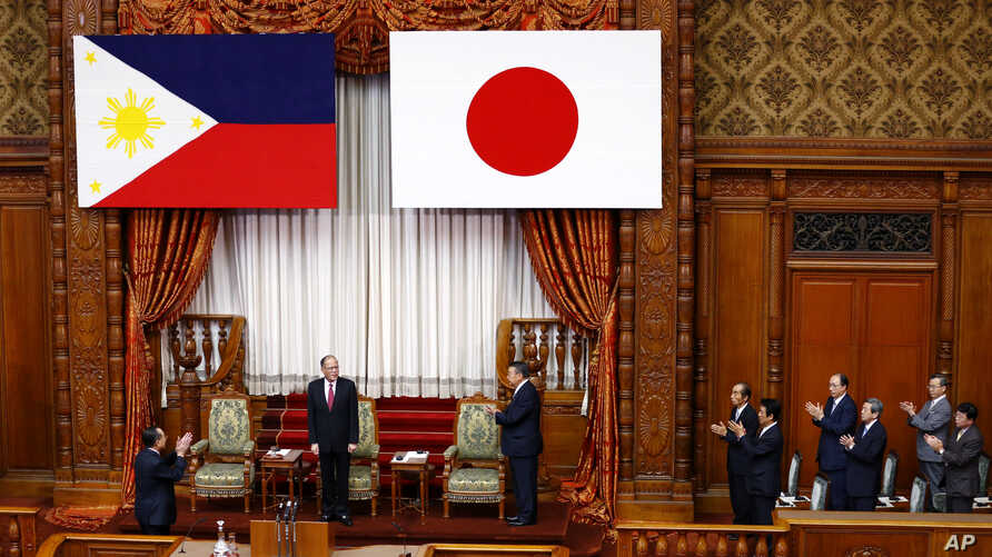 Philippine President Benigno Aquino III, second from left, is applauded by parliament members before addressing the upper house in Tokyo, Wednesday, June 3, 2015.