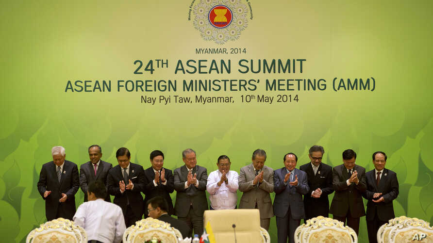Foreign Ministers and representatives of Association of Southeast Asian Nations, applaud after posing for a group photo during the 24th ASEAN summit in Naypyitaw, Myanmar, Saturday, May 10 2014.