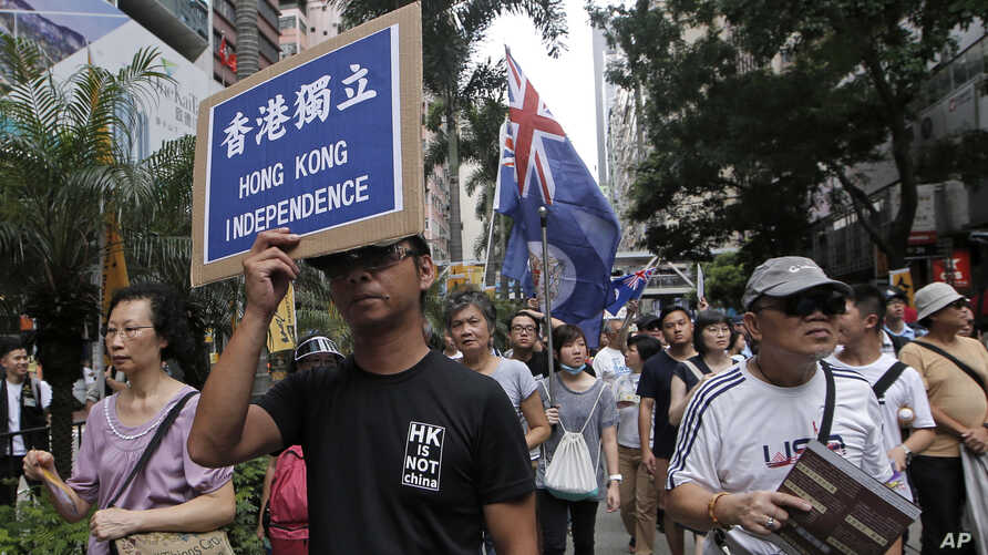 FILE - Protesters hold placards and wave Hong Kong colonial flags at an annual pro-democracy rally in Hong Kong, July 1, 2016. As the territory prepares for legislative elections, a new pledge of loyalty to China candidates are required to sign is be