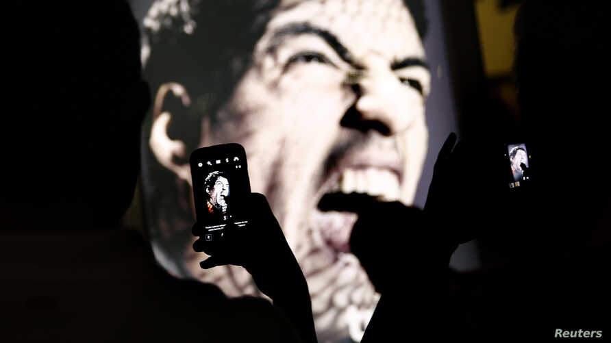 People use their mobile devices to take pictures of an advertising placard showing Uruguay's striker Luis Suarez flashing his teeth at, Copacabana beach in Rio de Janeiro June 26, 2014. Suarez was hit with the biggest ban imposed at a World Cup on Th