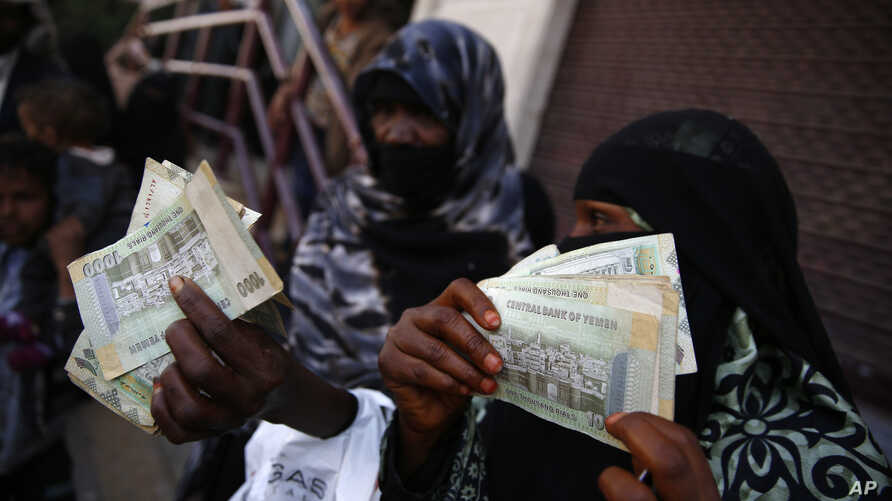FILE - Yemeni women display paper currency in Sanaa, Yemen.