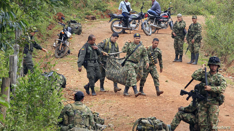 Colombian soldiers carry the weapons of comrades killed after a rebel attack in La Esperanza village, April 15, 2015.