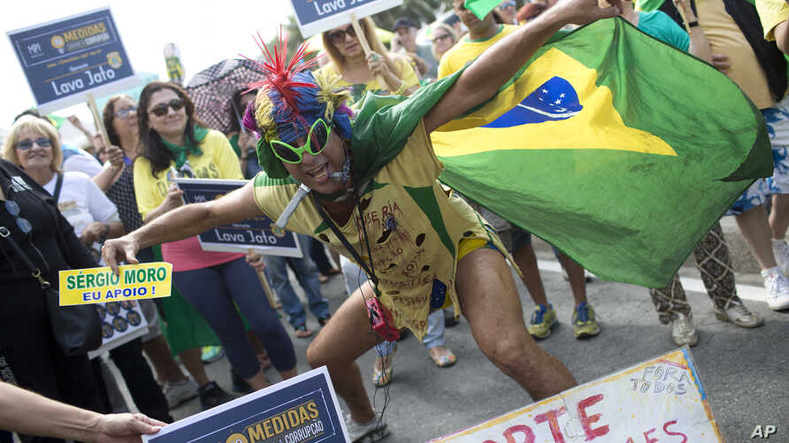 A demonstrator shouts slogans against suspended Brazilian President Dilma Rousseff during a protest demanding her impeachment, on Copacabana beach, in Rio de Janeiro, Brazil, Sunday, July 31, 2016.