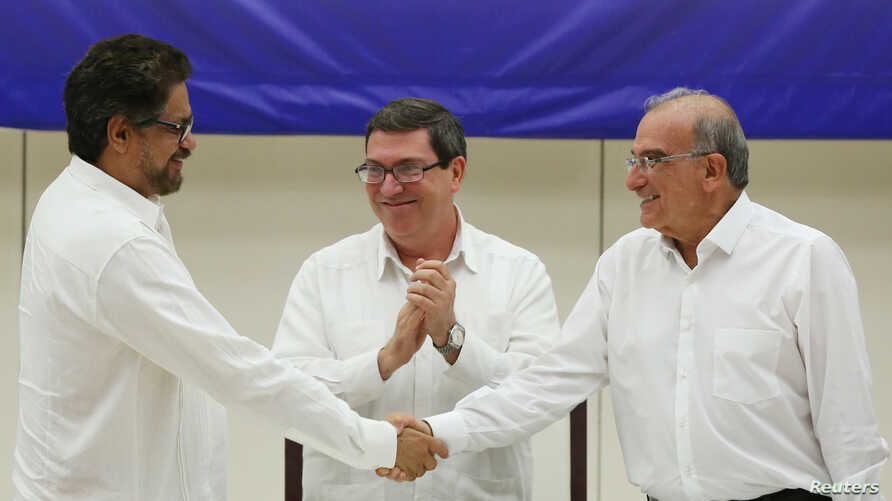 Lead FARC negotiator Ivan Marquez, left, and lead Colombian government negotiator Humberto de la Calle shake hands while Cuba's Foreign Minister Bruno Rodriguez looks on after the signing of a final peace deal in Havana, Cuba, Aug. 24, 2016.