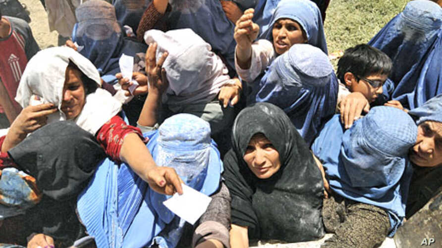 Afghan women stretch for food donations from the World Food Programme (WFP) in Kabul, (File)