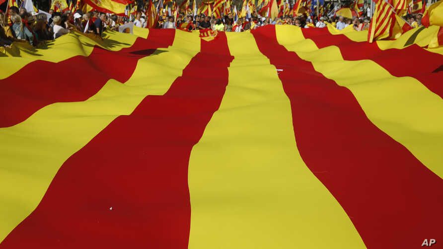 Nationalist activists protest with a giant Catalan flag during a mass rally against Catalonia's declaration of independence, in Barcelona, Spain, Oct. 29, 2017.