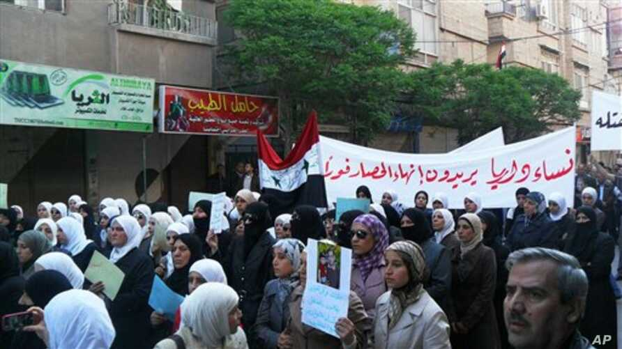In this citizen journalism image made on a mobile phone, Syrian women carry a banner in Arabic that reads:' the women of Darayya want an end to the siege,' as they protest in Darayya, southwest of Damascus, Syria, April 25, 2011