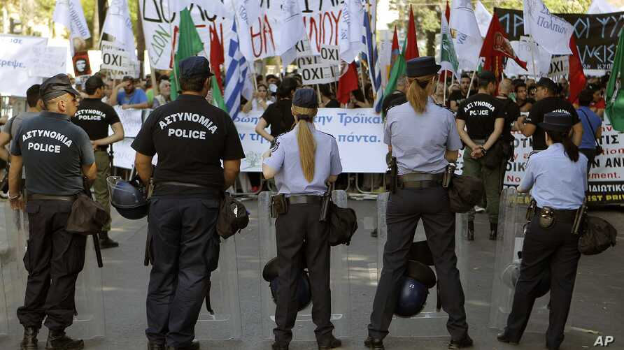 Police officers stand in front of the protesters during an anti-bailout protest outside of the Cyprus parliament in Nicosia, April 30, 2013.