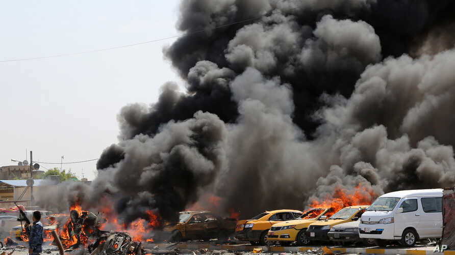 A police officer stands near burning vehicles moments after one in a series of bombs hit the Shi'ite stronghold of Sadr City, in Baghdad, May 13, 2014.