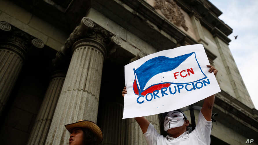 """A masked man holds up a sign that reads """"FCN Corruption,"""" referring to the ruling party, Frente Convergencia Nacional, as he and others protest Guatemala's President Jimmy Morales at Constitution square in Guatemala City, April 21, 2018."""