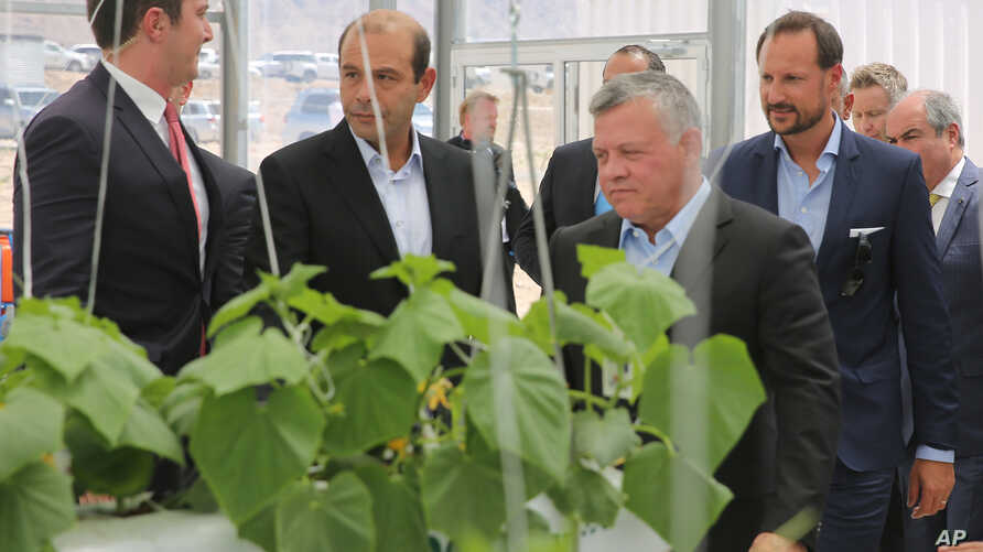 Jordan's King Abdaullah II and Norway's Crown Prince Haakon (to the right of and right behind Abdullah) listened to a briefing, Sept. 7, 2017 during a visit of a new facility in Jordan's Red Sea port city of Aqaba that produces crops from seawater, u
