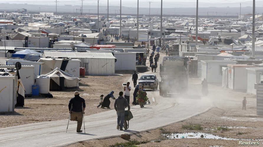 Syrian refugees walk at the Al Zaatari refugee camp in the Jordanian city of Mafraq, near the border with Syria, December 7, 2014.