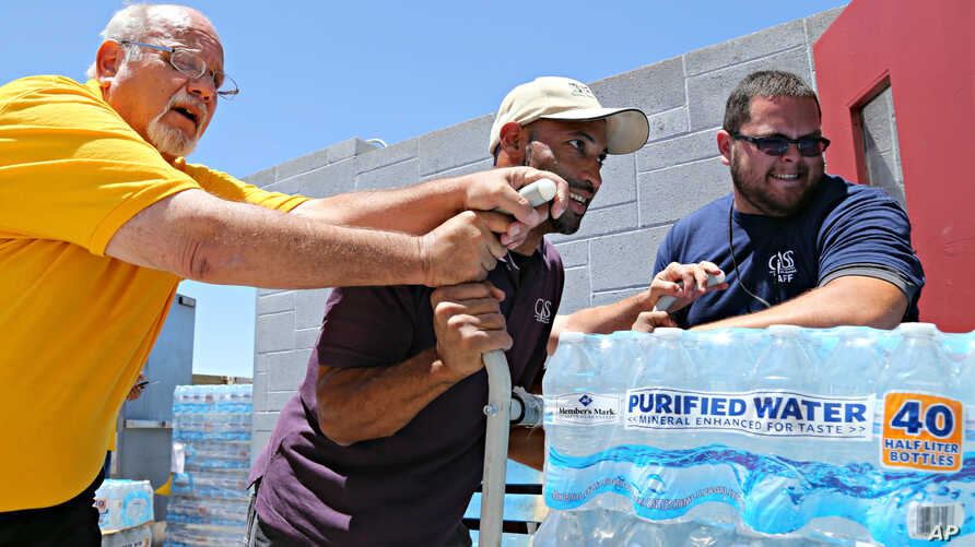 Leo Block, left, Matari Phason, center, and Brian Juarez push part of a shipment of 20,000 bottles of water donated by Yellow Cab of Phoenix to Central Arizona Shelter Services, Arizona's largest homeless shelter, to help prepare for the summer heat
