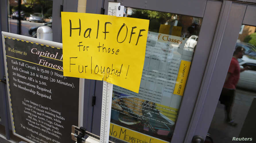 A sign at a fitness studio advertises a deal for furloughed government workers in the Capitol Hill neighborhood in Washington. Democrats and Republicans in the U.S. House of Representatives agreed on Saturday to retroactively pay 800,000 furloughed f