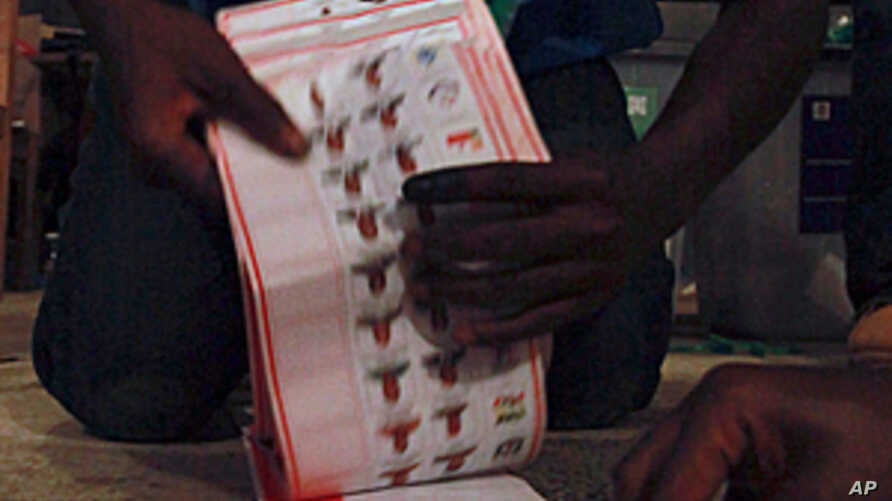 Polling agents count ballots for the Liberian presidential election at a polling station in Monrovia, October 11, 2011.