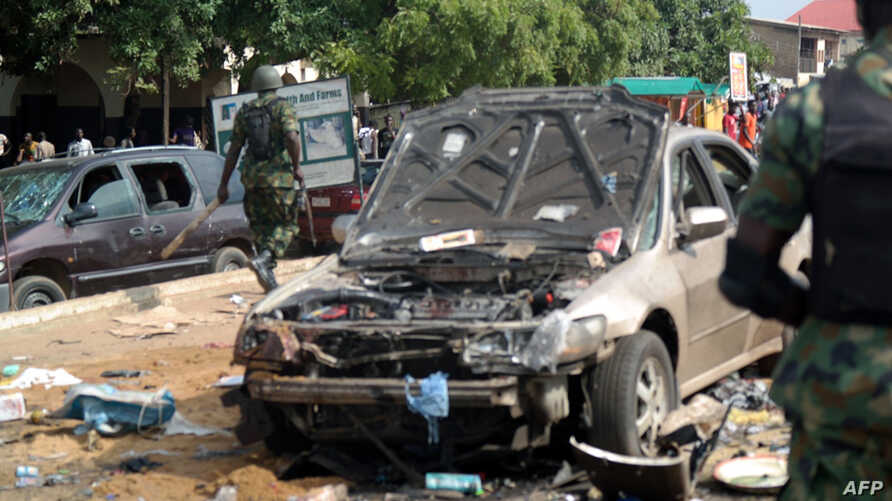 Military officers walk past scene of explosion in Kaduna, northern Nigeria, July 23, 2014.