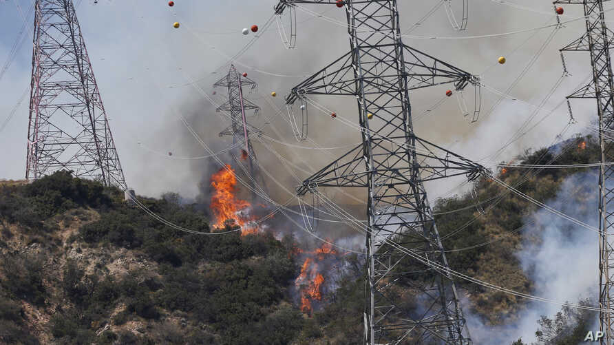 Smoke from wildfires rises from a hillside near power lines outside Azusa, Calif., Monday, June 20, 2016. New wildfires erupted Monday in Southern California and chased people from their homes as an intensifying heat wave stretching from the West Coa