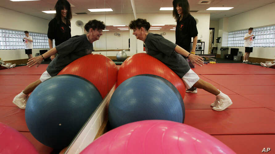 YMCA of Burlington County Wellness Director Joann Agoglia stands by as cancer survivor Clare Faber, of Mount. Holly, N.J.  works through an exercise program Tuesday, Aug.11, 2009, in Mount Laurel, N.J. (AP Photo/Mel Evans)