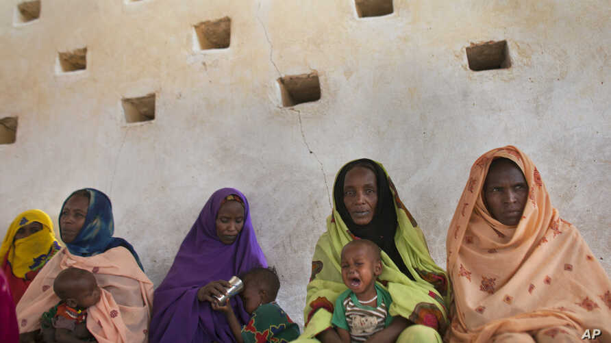Mothers wait for their children to be examined for signs of malnutrition at a walk-in nutrition clinic in Barrah, a desert village in the Sahel belt of Chad, Friday, April 20, 2012. UNICEF estimates that 127,000 children under five in Chad's Sahel be