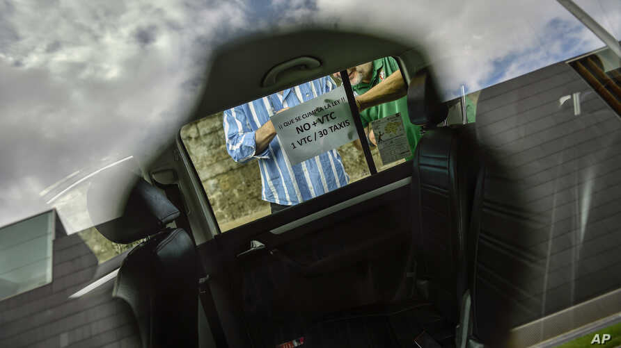 FILE - Drivers place a sign at the window of a taxi that demands compliance to the law for taxi service during a protest against the services of private companies, in Pamplona, northern Spain, May 30, 2017.