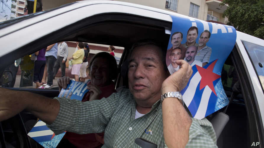 A man drives his car holding a poster with pictures of the Cuban Five, celebrating their freedom, in Havana, Cuba, Wednesday, Dec. 17, 2014. After a half-century of Cold War acrimony, the United States and Cuba abruptly moved on Wednesday to restore