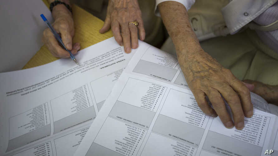 Voters inspect their ballots at a polling station in Zagreb, Croatia, Sept. 11, 2016.