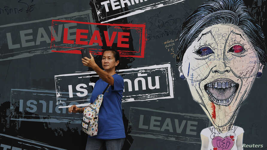 "A woman takes a ""selfie"" in front of a banner with a caricature of the caretaker Prime Minister Yingluck Shinawatra displayed inside an anti-government protest encampment in central Bangkok, Feb. 25, 2014."