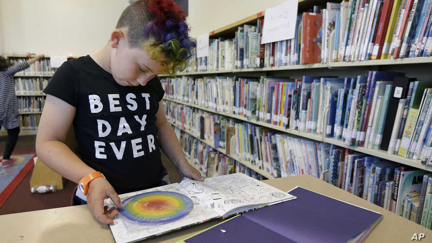 FILE - Sam, 9, reads a book in the library at Bay Area Rainbow Day Camp in El Cerrito, Calif., July 12, 2017.