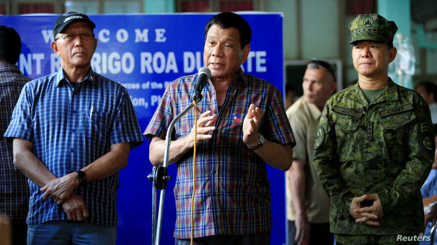 Philippines' President Rodrigo Duterte (C) with Defense Secretary Delfin Lorenzana (L) and General Eduardo Ano, talks after visiting wounded soldiers, at a military camp in Cagayan De Oro, June 11, 2017.