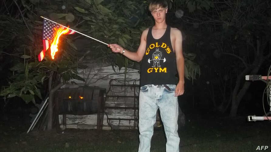 This undated photo taken from Lastrhodesian.com on June 20, 2015, allegedly shows Dylann Roof burning a U.S. flag. The site is no longer in operation.