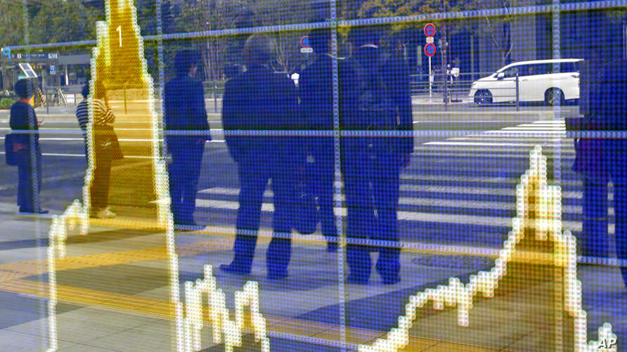 In this April 8, 2016 file photo, people are reflected on the electronic board of a securities firm in Tokyo. The IMF downgraded its outlook for growth for most regions and for the global economy as a whole.