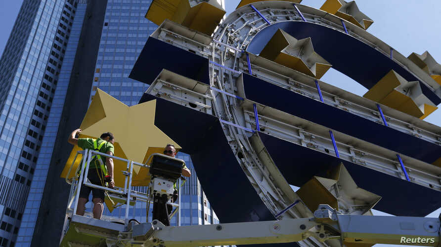 Workers dismantle the large euro sign sculpture for maintenance, in front of the headquarters of the former European Central Bank (ECB) in Frankfurt, July 6, 2015.