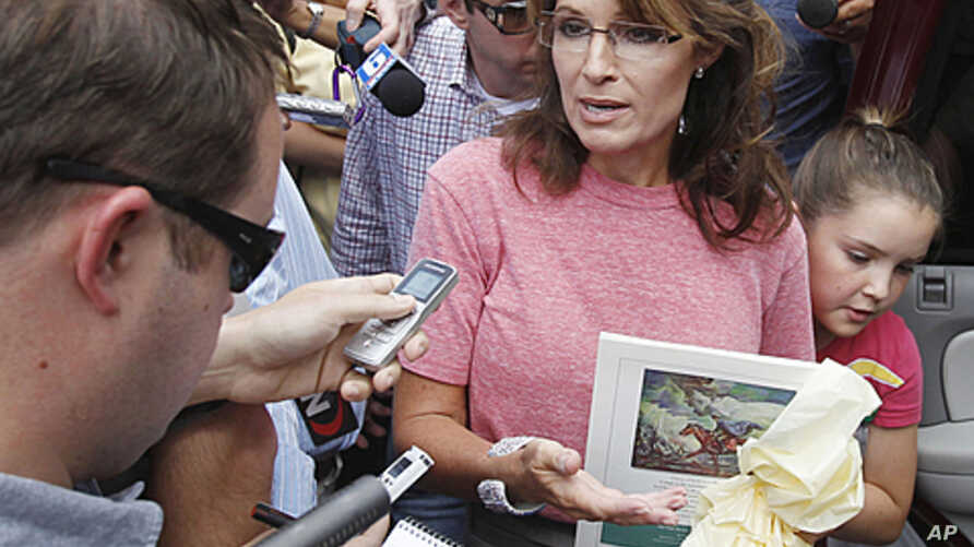 Former Alaska Governor Sarah Palin, holding a booklet depicting Paul Revere, speaks briefly with the media as she tours Boston's North End neighborhood, June 2, 2011 (file photo).