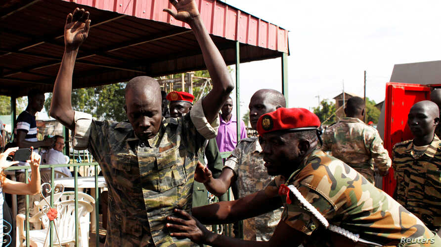 A South Sudanese soldier is checked as he arrives for a sentencing over the rape of foreign aid workers and the murder of a local journalist in an assault on the Terrain Hotel in the capital Juba in 2016 at a military court in Juba, South Sudan, Sept