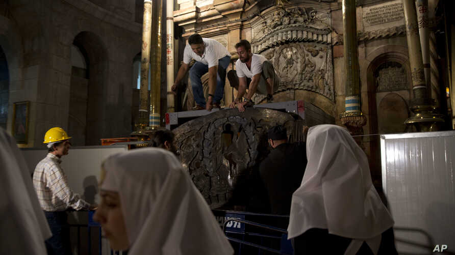 FILE - Christian nuns watch as experts begin renovation of Jesus' tomb in the Church of the Holy Sepulchre in Jerusalem's old city, June 6, 2016. The team has begun a historic renovation at the spot where Christians believe Jesus was buried, overcomi