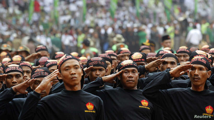 Members of Banser, the security unit of Indonesia's largest Muslim organization, Nahdlatul Ulama (NU), salute guests during a parade to commemorate the organization's 85th anniversary in Gelora Bung Karno Stadium in Jakarta, July 17, 2011.