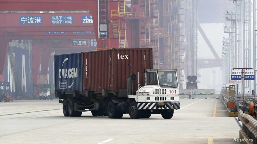 A trailer loaded with container boxes travels in Ningbo port in Zhejiang province