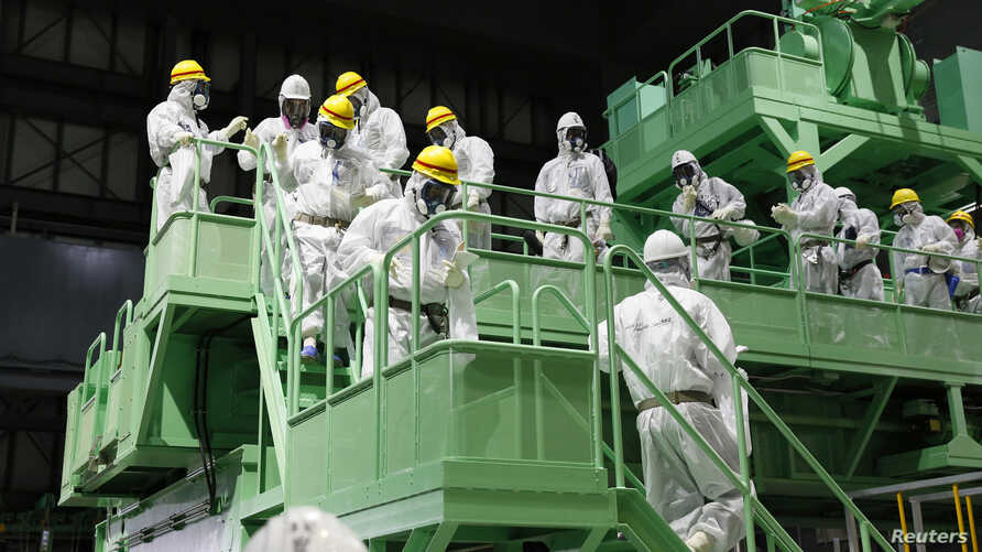 Members of the media and Tokyo Electric Power Co. (TEPCO) employees wearing protective suits and masks walk down the steps of a fuel handling machine on the spent fuel pool inside the No.4 reactor building at the tsunami-crippled TEPCO's Fukushima Da