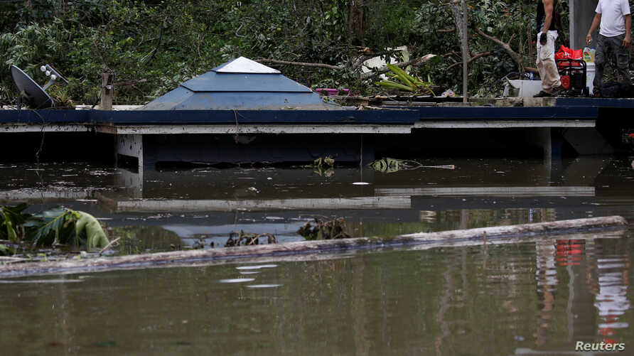 Men stand at the roof of a house submerged by floodwaters close to the Guajataca Dam after the area was hit by Hurricane Maria in Guajataca, Puerto Rico, Sept. 23, 2017.