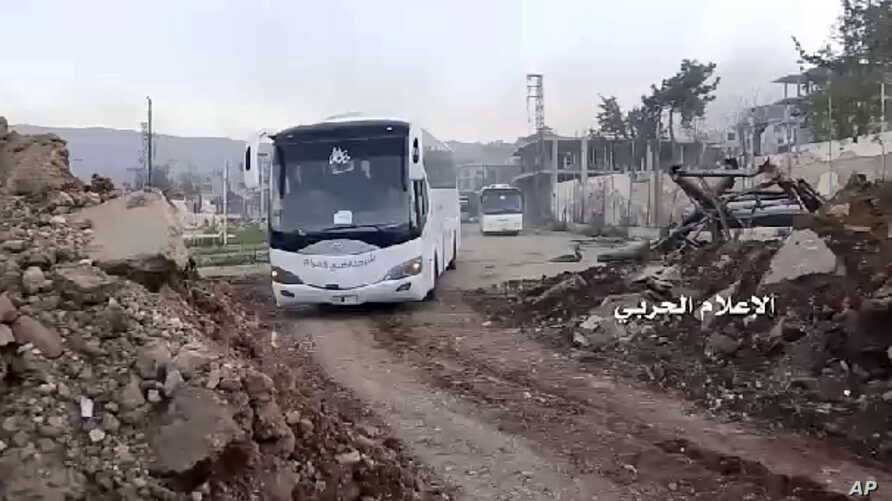 This frame grab from video provided by the government-controlled Syrian Central Military Media, shows buses carrying opposition fighters leaving Zabadani, near Damascus, Syria, April. 19, 2017, heading toward the northern rebel-held Idlib province.