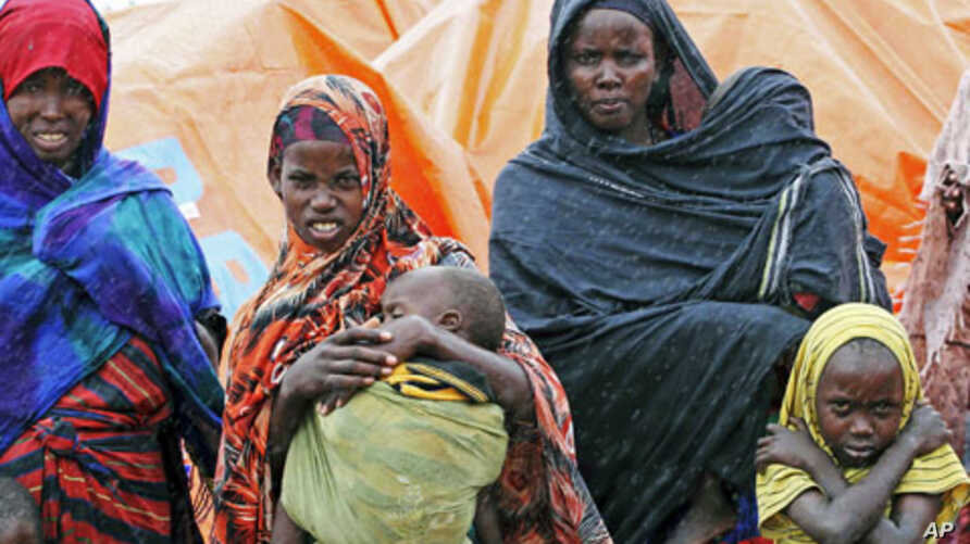 An internally displaced Somali family stand in the rain outside their makeshift shelter in the south of Mogadishu's Hodan district, August 2, 2011