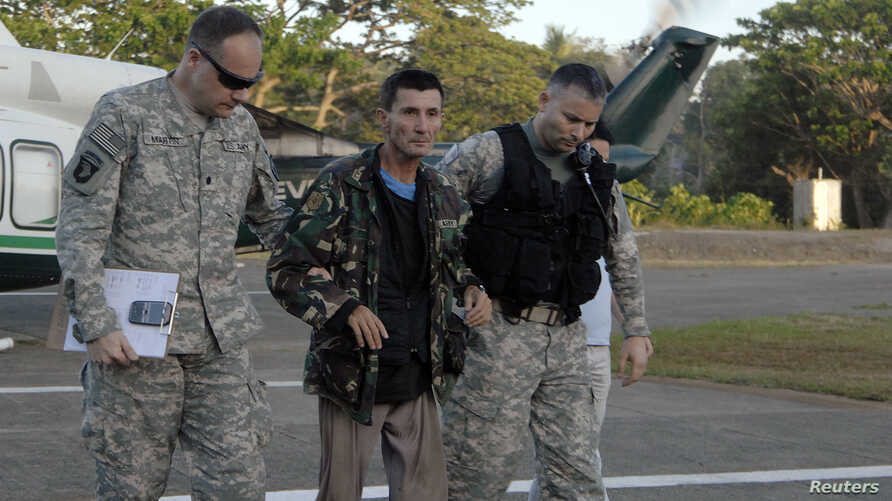 U.S. military servicemen assist freed Australian national Warren Richard Rodwell after he gets off a helicopter inside a military camp in Zamboanga City, southern Philippines, March 23, 2013, in this picture provided by the Western Mindanao Command o